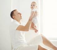 El padre feliz que se sostiene encendido da su bebé en casa en el sitio blanco Foto de archivo
