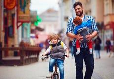 El padre feliz y dos hijos en la ciudad caminan Licencia parental Bebé fotografía de archivo