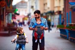 El padre feliz y dos hijos en la ciudad caminan Licencia parental Bebé fotografía de archivo libre de regalías