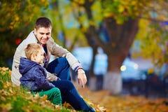 El padre feliz y el hijo que se sientan en otoño parquean Foto de archivo