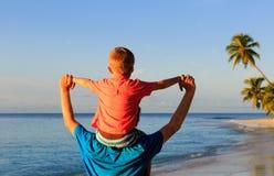 El padre feliz y el pequeño hijo en hombros juegan en la playa Imagenes de archivo