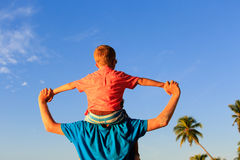 El padre feliz y el pequeño hijo juegan en el cielo en la playa Imágenes de archivo libres de regalías