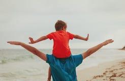 El padre feliz y el pequeño hijo juegan en el cielo en la playa Fotografía de archivo libre de regalías