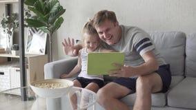 el padre feliz y la pequeña hija con la tableta dicen en Skype metrajes