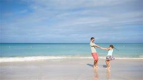 El padre feliz y su pequeña hija adorable en la playa arenosa blanca se divierten La familia disfruta de vacaciones en costa del  almacen de metraje de vídeo