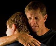 El padre, gritando, abraza al hijo Imagenes de archivo