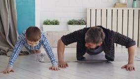 El padre hermoso activo y su hijo alegre están ejercitando haciendo la prensa-para arriba juntos en casa en piso de madera Famili almacen de metraje de vídeo