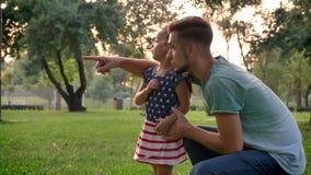 El padre hermoso está señalando a su pequeña hija en madre, ella corre a ella, concepto de familia metrajes