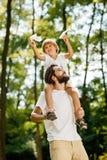 El padre hermoso y su pequeño el hijo que caminan en el muchacho del bosque se está sentando en los hombros de su padre y mantien fotos de archivo libres de regalías