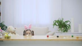 El padre infantil y su hija con los oídos del conejito en su cabeza están ocultando debajo de la tabla de madera, por completo de