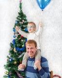 El padre joven con el muchacho divertido en el suyo lleva a hombros cerca de abeto del Año Nuevo Foto de archivo