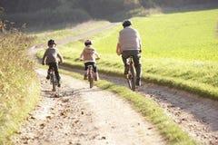 El padre joven con los niños monta las bicis en parque Fotografía de archivo