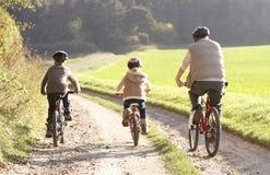El padre joven con los niños monta las bicis en parque Imagen de archivo