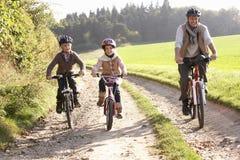 El padre joven con los niños monta las bicis en parque Imagen de archivo libre de regalías