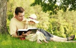 El padre joven con su pequeña hija lee la biblia fotos de archivo libres de regalías
