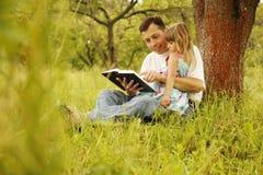 El padre joven con su pequeña hija lee la biblia imagen de archivo