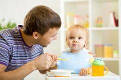 El padre joven enseña a su hijo del bebé a comer con Foto de archivo libre de regalías