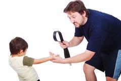 El padre joven está castigando a su pequeño hijo aislado imagen de archivo libre de regalías
