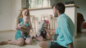 El padre joven está jugando con su pequeño hijo de la hija y del bebé, mientras que su esposa está deteniendo al bebé Cámara lent almacen de video