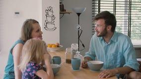 El padre joven está mirando su esposa e hija la tabla de cocina durante la cámara lenta del desayuno, tiro de Steadicam almacen de video