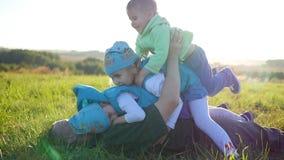 El padre joven feliz con sus niños miente en el césped en el parque Juego de tres niños feliz con su padre Niños almacen de video