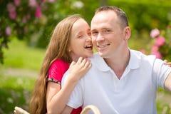 El padre joven hermoso y la pequeña hija bonita abrazan al aire libre Fotos de archivo