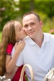 El padre joven hermoso y la pequeña hija bonita abrazan al aire libre Imagen de archivo libre de regalías