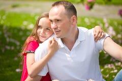 El padre joven hermoso y la pequeña hija bonita abrazan al aire libre Imagen de archivo