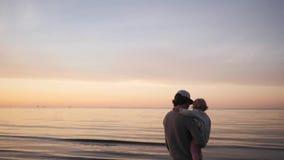 El padre joven juega con poca hija en los abrazos de la playa y las risas, lanzan para arriba metrajes