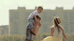 El padre joven que detiene a su hijo en los hombros gira alrededor Mime a caminar adentro para besar a su pequeño hijo almacen de metraje de vídeo