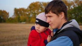 El padre joven que detiene a su niño en las manos y mira la puesta del sol Dulzura y abrazo del padre querido outdoor almacen de video
