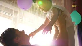 El padre joven que juega con el bebé, deteniéndolo en mis brazos, lanza para arriba Rayos de Sun a través de la ventana Risa y al almacen de metraje de vídeo