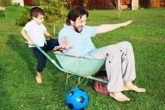 El padre joven y el pequeño hijo son el jugar al aire libre imagen de archivo libre de regalías