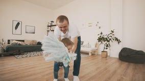 El padre joven y el pequeño hijo se divierten en casa con el caballo del juguete en la cámara lenta metrajes