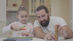 El padre joven y su pequeña hija linda se están sentando en sala de estar y están mirando un experimento con los marcadores y el  almacen de metraje de vídeo