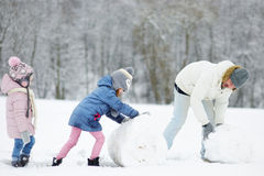 El padre joven y sus dos hijas en invierno parquean fotos de archivo libres de regalías