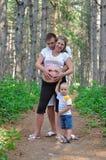 El padre, la madre embarazada y el niño en la madera de pino Fotos de archivo libres de regalías