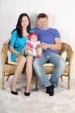 El padre, la madre y el bebé jovenes felices se sientan en el sofá en casa. Fotos de archivo libres de regalías