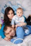 El padre, la madre y el hijo en una cama Imágenes de archivo libres de regalías