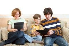 El padre, la madre y el hijo se sientan con los dispositivos electrónicos Fotos de archivo libres de regalías