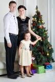 El padre, la madre y la hija colocan el árbol de navidad cercano Fotografía de archivo