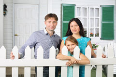 El padre, la madre y la hija felices se colocan al lado de la cerca blanca Imagen de archivo libre de regalías