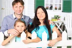 El padre, la madre y la pequeña hija se colocan al lado de la cerca Fotos de archivo