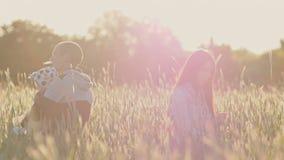 El padre, la madre y la pequeña hija disfrutan de la naturaleza juntos en un campo del trigo entre las espiguillas verdes En los  metrajes