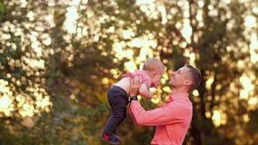 El padre lanza para arriba al hijo en la naturaleza almacen de metraje de vídeo