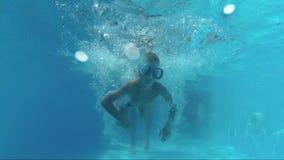 El padre lanza para arriba al hijo en la piscina para un salto metrajes