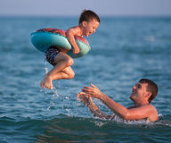 El padre lanza para arriba a su hijo en un círculo inflable bajo el mar Imágenes de archivo libres de regalías