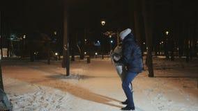 El padre lanza para arriba a su pequeña hija en parque del invierno de la tarde metrajes
