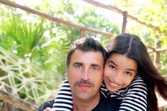 El padre latino hispánico y la hija adolescente abrazan el parque Foto de archivo