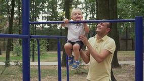El padre levanta a su poco hijo en la barra horizontal metrajes